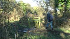 Walker on public right of way footpath crossing a stile rural setting Stock Footage