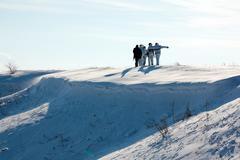 Hunters walking in snow - stock photo