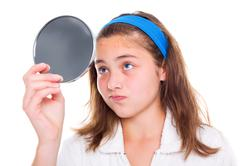Girl examine her pimples in the mirror - stock photo