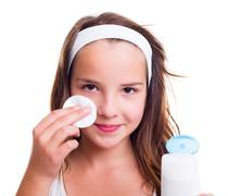 Girl cleaning her face with tonic lotion - stock photo