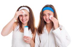 Girls cleaning theirs face with tonic lotion Stock Photos
