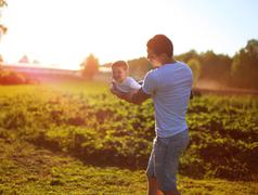 Happy child, dad and son having fun, holding on hands on a sunset background Stock Photos