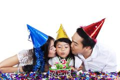 Parents kissing their child in birthday party - stock photo