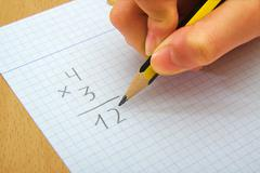 Stock Photo of Closeup on the hands of a child doing maths. Multiply. School concept