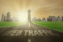 Road rises upward with web traffic text - stock photo