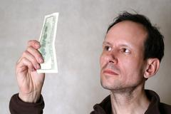Checks dollars on authenticity - stock photo