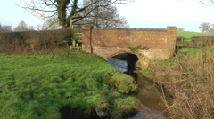 Red bridge over stream with stile rural setting - stock footage