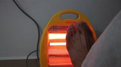 Warming up legs by heater Stock Footage