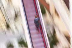 woman on a moving staircase in the shopping center - stock photo