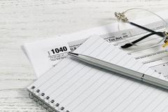 Pen and paper with tax forms on white desktop Stock Photos