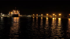Sailing Past Cargo Ship A Port On Dark Night Wide Shot Stock Footage