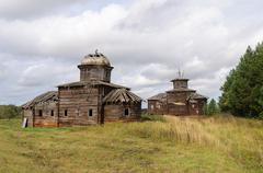 Two ancient destroyed wooden churchs in northern russian village Stock Photos