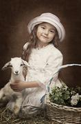 Portrait of a little girl with a baby goat - stock photo