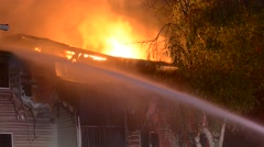 House fire severe damage lots of flames firehouse spraying Stock Footage