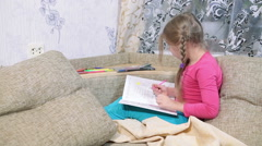 Young girl drawing in color book with pencils while sitting on couch in room Stock Footage