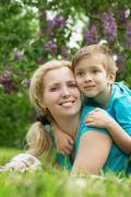 Woman lying with son on green grass - stock photo