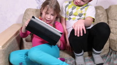 Kids playing with pad, sitting together on couch in domestic room Stock Footage