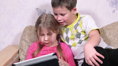 Caucasian kids playing with pad, sitting together on couch in domestic room Stock Footage