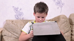 Preschool Caucasian boy turning pad while playing the game, sitting on the sofa  Stock Footage