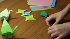 Hands Of Child Folding Origami Frog With Green Paper Stock Footage