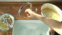 Placing dirty dishes in sink. Stock Footage