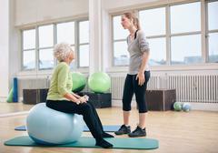 Physical therapist instructing a senior woman at rehab Stock Photos