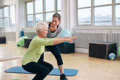 Elderly woman doing exercise with her personal trainer Stock Photos