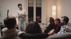 Man playing charades with friends at home Stock Footage