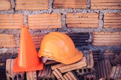 construction helmet safety and cone in construction site with bricks - stock photo