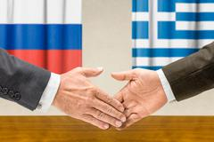 Representatives of Russia and Greece shake hands - stock photo