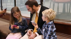 Father teaching children how to use cellphones - stock footage