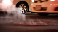 Manhole cover billows steam on Boston city street Stock Footage