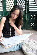 Young female sitting and studying alone. Stock Photos