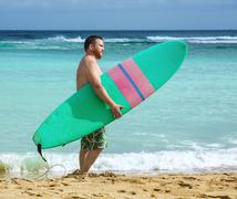 Man holding surf board standing near the ocean Stock Photos