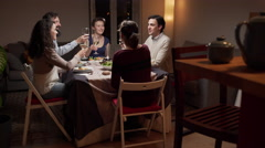 Friends toast and celebrate at dinner Stock Footage