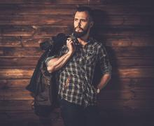 Handsome man wearing checkered  shirt and waxed canvas jacket Stock Photos