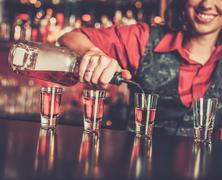 Beautiful redhead barmaid making shots Kuvituskuvat