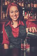 Beautiful redhead barmaid making cocktail Kuvituskuvat