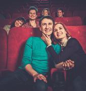 Group of smiling people watching movie in cinema Kuvituskuvat
