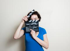 Smiling girl with movie clapper on white background Stock Photos