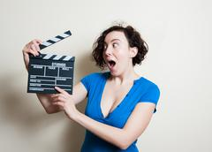 Girl with funny face and movie clapper on white background Stock Photos