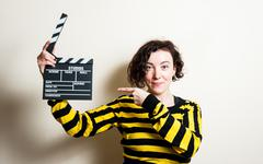 Girl smiling pointing out movie clapper on white background Stock Photos