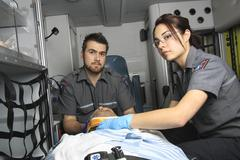 professional paramedics giving unconscious young woman first aid - stock photo