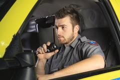 A paramedic at the wheel of his ambulance talking on microphone Stock Photos