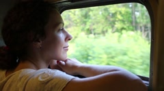 Happy curly woman looks in train window during travel - stock footage