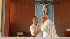 Sacristan assists priest vestment Stock Footage
