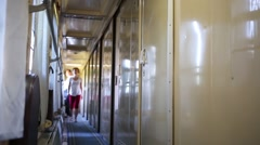 Young woman goes along corridor of modern train carriage Stock Footage