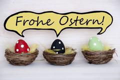 three colorful easter eggs in baskets with german Frohe Ostern - stock photo