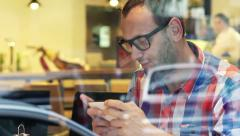 Young, handsome man playing game on smartphone sitting in cafe HD Stock Footage