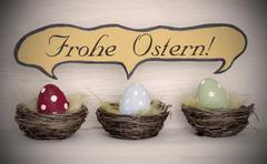 Three colorful easter eggs baskets with german Frohe Ostern Stock Photos
